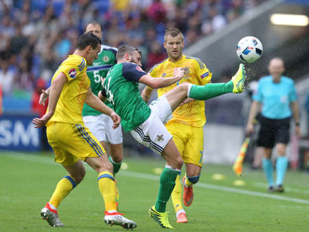 LYON, FRANCE - JUNE 16, 2016: Stuart Dallas of Northern Ireland (C) fights for a ball with Ukrainian players during their UEFA EURO 2016 game at Stade de Lyon stadium. N.Ireland won 2-0