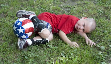 Young boy on the ground with soccer ball  Stock Photo