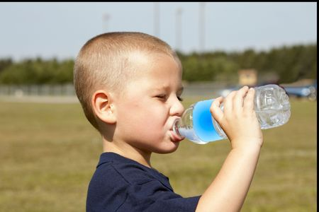 Young thirsty boy getting a drink of clear cold water