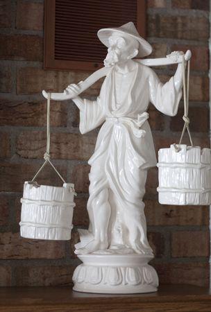 Statue of older man balancing water on his shoulders