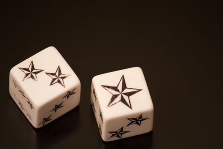Two dice with stars on black backround Stock Photo