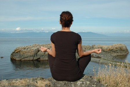 Woman in Yoga pose overlooking the ocean