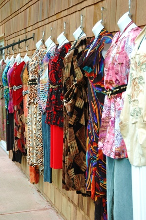 A row of womens outfits hanging on display