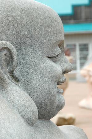 A closeup of a stone statue of Buddhas face