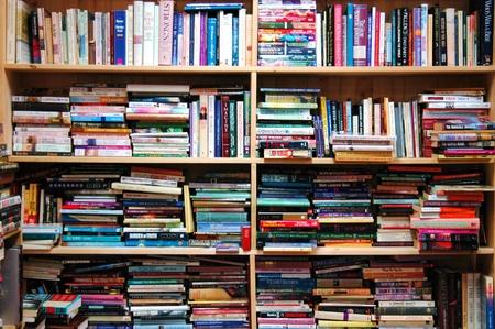 shelf: A book shelf overloaded with an assortment of books