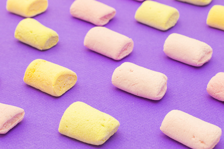 Pattern with yellow and purple yummy marshmallows on violet background