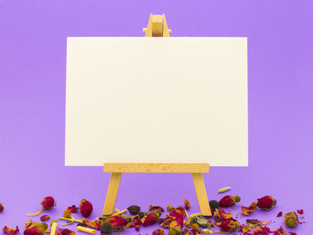 White paper on little easel on colorful violet background with little roses Stock Photo