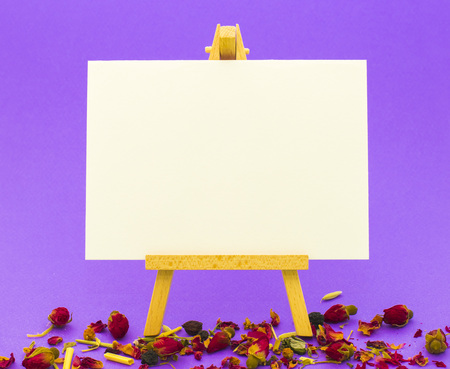 White paper on little easel on colorful violet background with little roses 版權商用圖片
