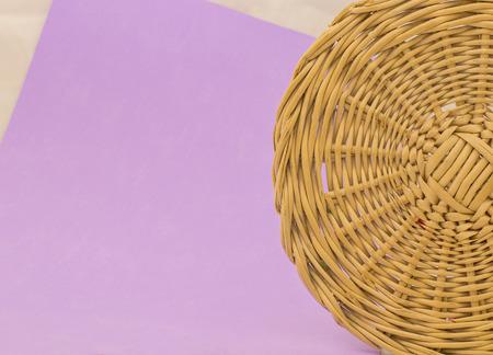 Hand wicker basket on purple background