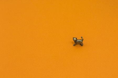 Little steam metal figure of cat on orange background 版權商用圖片