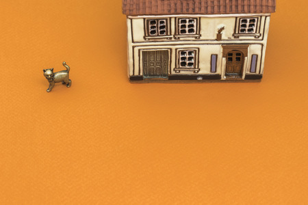 Little toy house with small metal cat on orange backgrounds