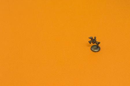 Little steam metal figure of horseman on orange background