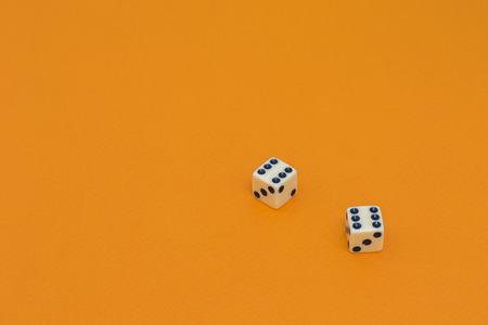 Isolated white dice on a orange background