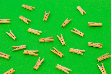 Set of wooden clothespins on bright green background