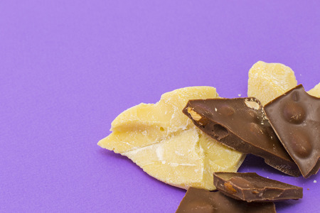 Milk chocolate with almond and cocoa butter on violet background 版權商用圖片
