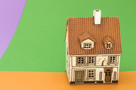 Little toy house on orange green and violet backgrounds