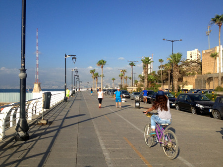 lebanon beach: Beirut, Lebanon - June 19, 2015: Peoplere walking via Beiruts famous seaside promenade and one girls biking in sunny day with the sea lantern at the background.