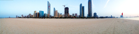 sand beach: Abu Dhabi, United Arab Emirates - March 14, 2015: Skyline with Skyscrapers in Abu Dhabi, United Arab Emirates from the public beach at the Corniche. White beach and blue clear water in the front.