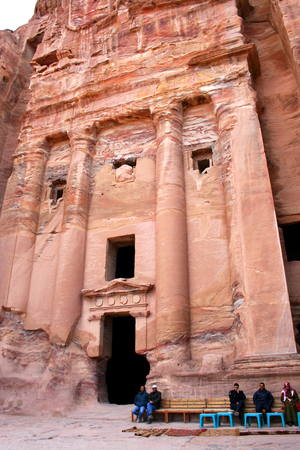 nabataean: Petra, Jordan - December 11, 2012: People are sitting near entrance into tombs carved into the red sandstone in Petra, Jordan. Ancient city, capital of the Nabataean kingdom - city of Petra in Jordan