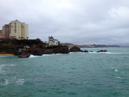 major ocean: Atlantic ocean and rocky coastline in Biarritz, France. A big oldstyle hotel on the coast.