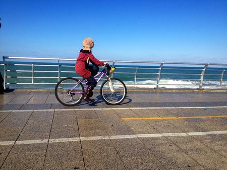 lebanon beach: Strolling on the Seaside promenade in Beirut. Beirut, Lebanon - January 09, 2016: one girls biking walking via Beiruts famous seaside promenade, Lebanon