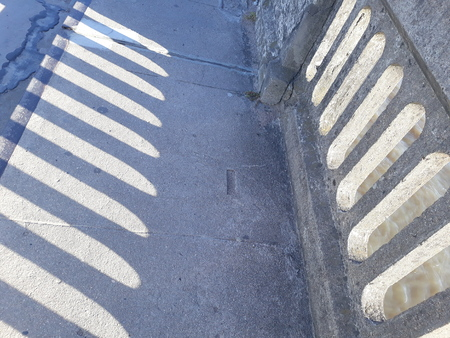 wall and its shadow, side by side, registered on the pavement floor
