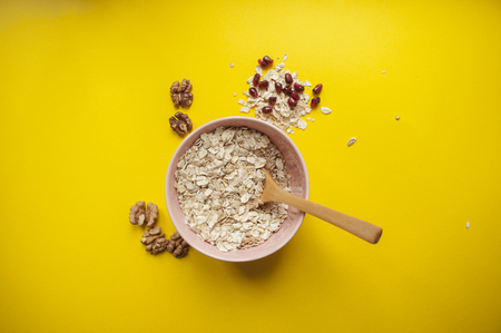 Oatmeal in a beautiful pink bowl with wooden spoon, pomegranate seeds and nuts around on bright yellow background.