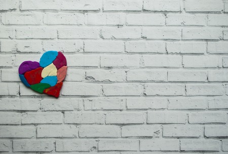 Autism awareness concept with colorful heart made of pieces of modeling clay on white background with text space.