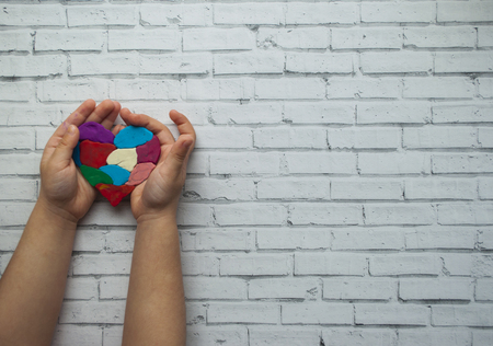 Las manos del niño sosteniendo un corazón multicolor como símbolo del día de la conciencia del autismo sobre fondo blanco con espacio de texto. Foto de archivo