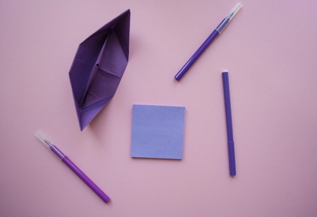 Paper ship, a notebook of violet color and markers on pastel violet background with text space.
