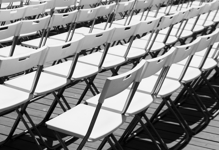 Rows of white empty folding chairs in a summer theatre. Imagens