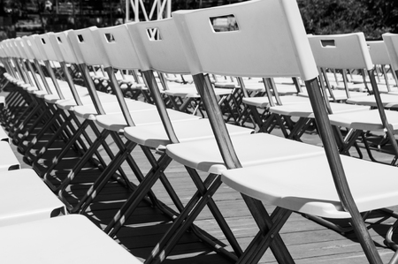 Minimalistic picture of rows of white empty folding chairs in a summer theatre. Banque d'images