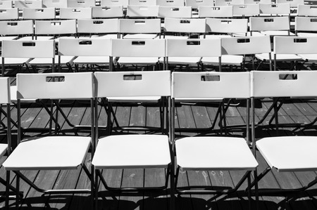 Rows of empty white seats organized for an outdoor event.