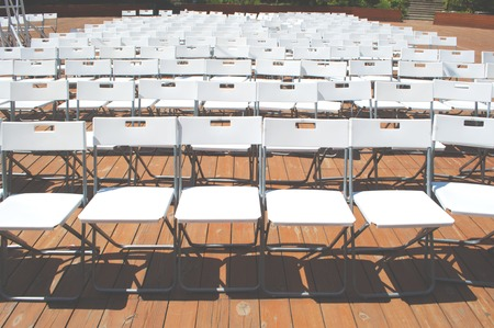 Rows of empty white seats for an outdoor event.