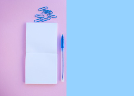 Back to school concept. Noteblock, pen and paper clip on pink and blue background with text space.