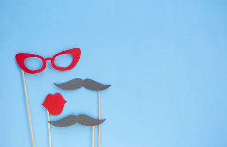 Photo booth props glasses, moustaches and lips on blue background.