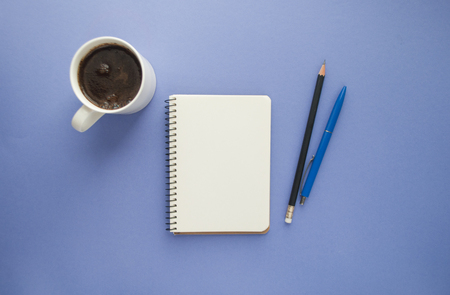 Flat lay of notepad, pens and a cup of coffee on purple background with copyspace.