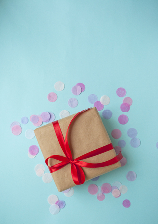 Gift box tied with red ribbon on pastel blue background.