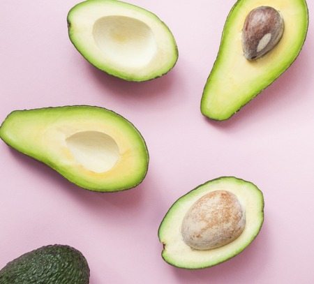 Halved avocado on pastel pink background.