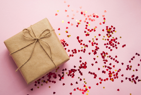 Gift box wrapped in brown colored craft paper and tied with rope on pink background with heart shape red confetti. 免版税图像