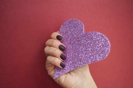 Young womans hand with beautiful manicure on dark red background holding pink glittering heart.