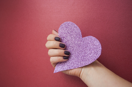 Young woman's hand with beautiful manicure on dark red background holding pink glittering heart.