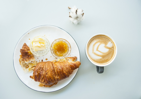 Falt lay of fresh croissant with jam, butter and cappuccino with beautiful latte art on grey table in a cafe. Morning routine.