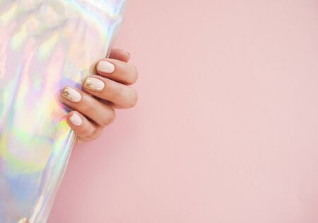 Young woman's hand with beautiful manicure on pink background holding metallic holographic paper.