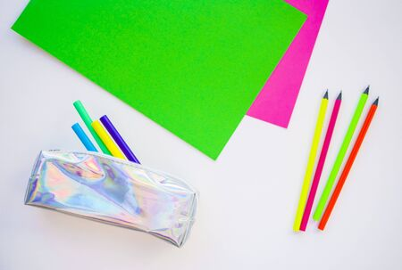 Colorful paper, neon pencils and holographic pencil case on beige background with copyspace. Flat lay style. Back to school concept.