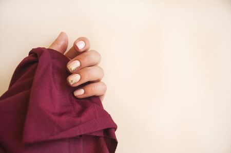 Young woman's hand with beautiful manicure on beige color background holding dark red color fabric. Stock Photo