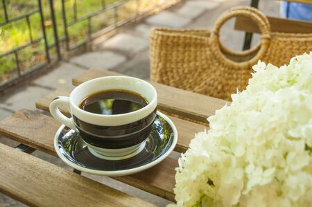 A cup of black coffee on a wooden table and a straw bag with hydragea flowers on the background. Reklamní fotografie
