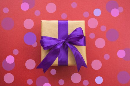 Giftbox tied with purple color ribbon on dark red background with beautiful confetti. Flat lay style.