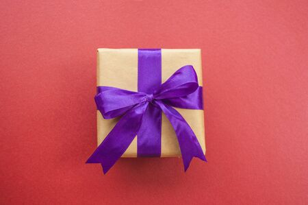 Giftbox tied with purple color ribbon on dark red background. Flat lay style. Stock Photo