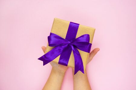Childs hands holding giftbox tied with purple color ribbon on pastel pink background. Flat lay style.